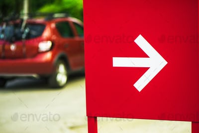 Direction arrow sign with car in background