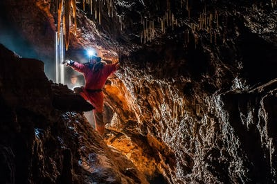 Spelunker discovering water underground in a cave