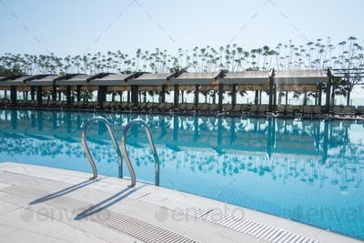 Swimming pool with sunshades and lounge chair