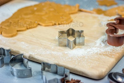 Making christmas gingerbread cookies. Dough and metal cutters on wooden table, horizontal