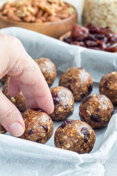 Healthy energy balls with cranberries, nuts, dates and rolled oats on tray, vertical