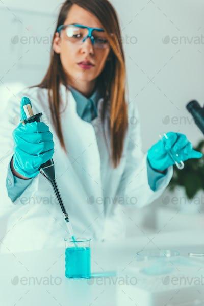 Laboratory technician with micro pipette