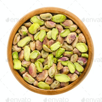 Shelled pistachio kernels in wooden bowl over white