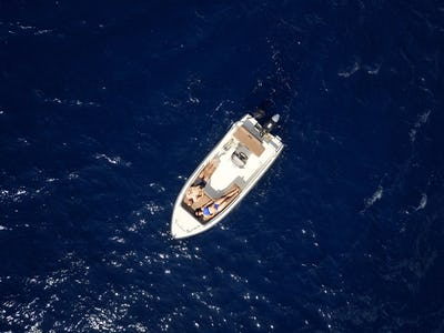 Aerial survey of a couple on a boat sunbathe together on a warm