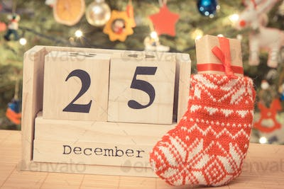 Date 25 December on calendar, gift in sock and christmas tree with decoration