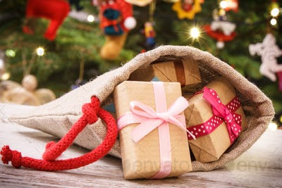 Wrapped gifts with ribbons in jute bag for Christmas and tree with decoration