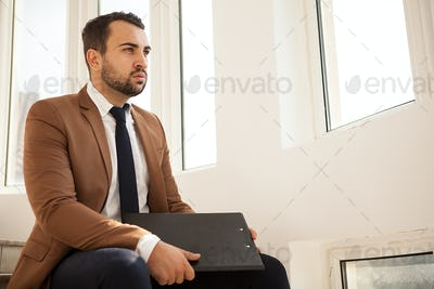 Succesful businessman sitting on stairs with a folder in hands