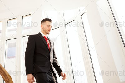 Portrait of young businessman walking on stair