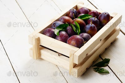 Wooden crate with plums