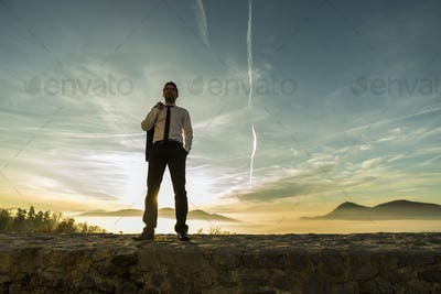 Businessman standing outdoors with his jacket over his shoulder