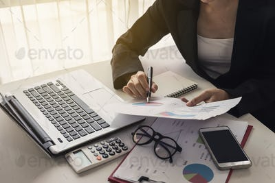 Businesswoman analyzing financial report with laptop