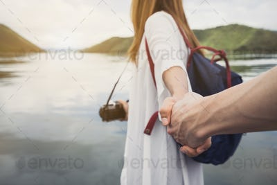 Young woman with camera holding man's hand