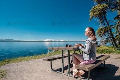 Woman tourist having a breakfast by Yellowstone Lake