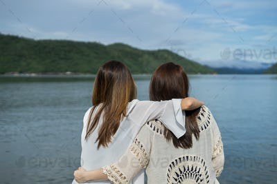 Two young women friends relaxing on wooden pier