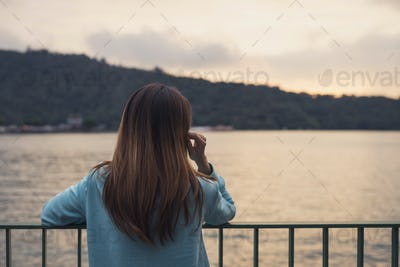 Lonely woman standing absent minded at the river