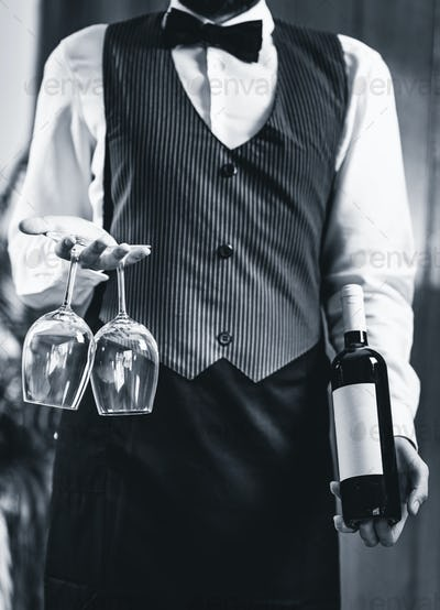 Sommelier holding wine bottle and wine glasses
