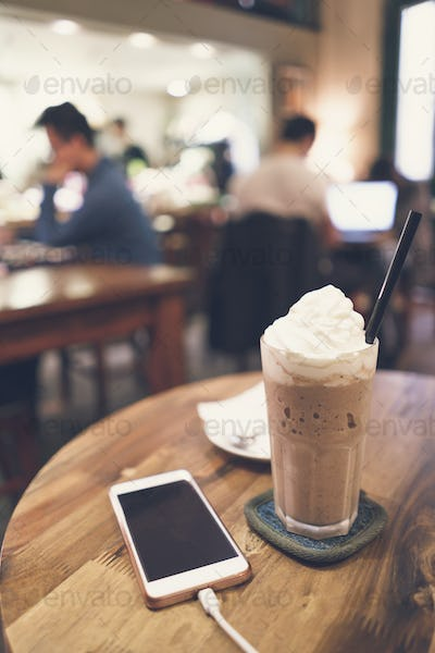 Cellphone and drinks on wooden table in coffee shop