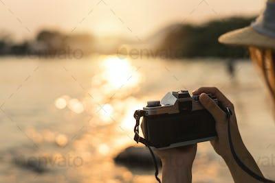 Hand holding camera to take photo of the beautiful sunset