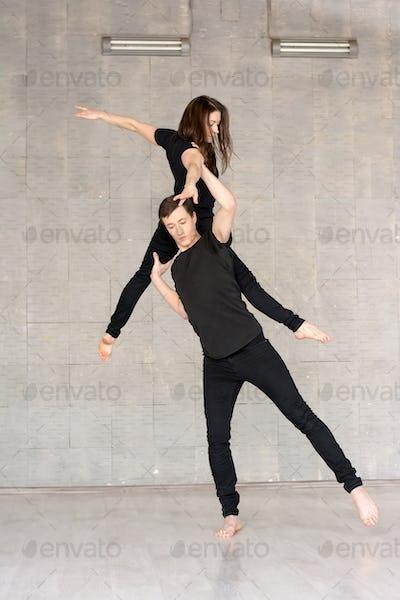 Young couple practices acrobatic balance