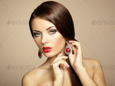 Portrait of beautiful brunette woman with earring. Perfect makeu