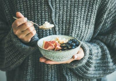 Woman in woolen sweater eating rice coconut porridge