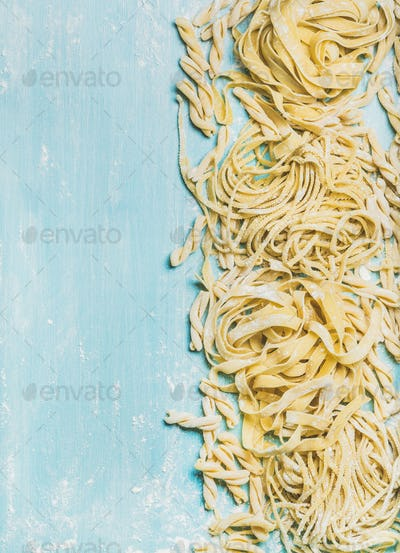 Various homemade uncooked Italian pasta with flour on blue background