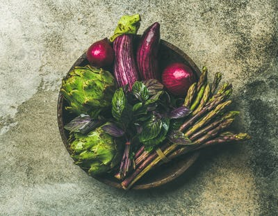 Flat-lay of green and purple vegetables on plate, grey background