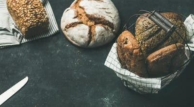Various bread loaves over black background, copy space, horizontal composition