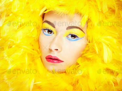 Portrait of beautiful girl in yellow feathers. Perfect makeup