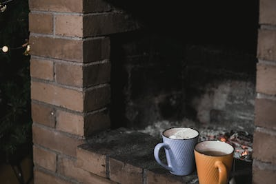 Two cups of tea with marshmallow against the background of a fireplace