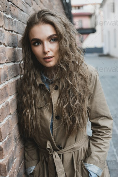 nice girl standing nearby brick wall outside