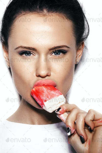Portrait of cute brunette girl eating ice cream