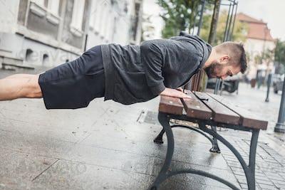 Man doing push-ups on a bench.