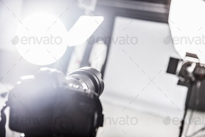 Photograpy studio with lighting equipment and a camera.