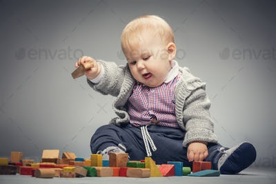Toddler boy playing with building blocks.