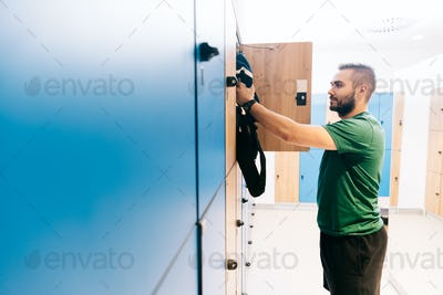 Man packing his gym bag into a blue locker
