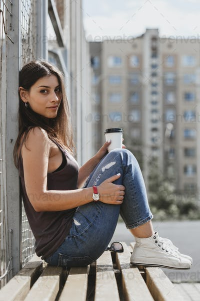 cute nice girl sitting nearby fence and drink coffee