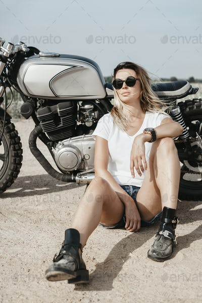 Sexy girl biker and cafe racer motorcycle
