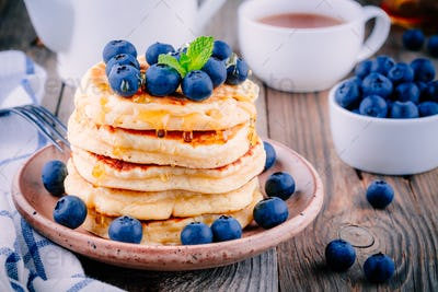 Delicious pancakes with fresh blueberries and honey