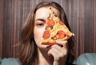 female face near pizza slice