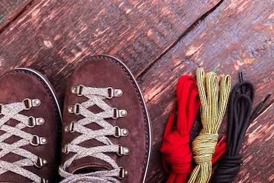 Brown man suede boots and shoelaces on wooden background. Flat lay. Autumn or winter shoes.
