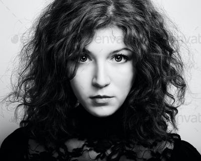 Portrait of the young beautiful woman with curly hair