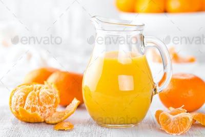 Tangerines, peeled tangerines and tangerine juice in glass. Mandarine juice.