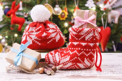 Gift for Christmas with red sock and cap, christmas tree with decoration, festive time concept