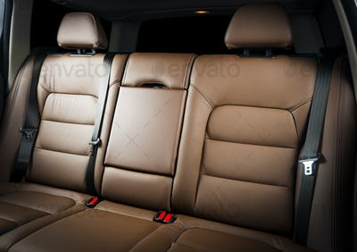 back seats of modern luxury car, red leather interior