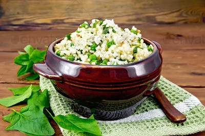 Couscous with spinach and green peas in bowl on wooden board