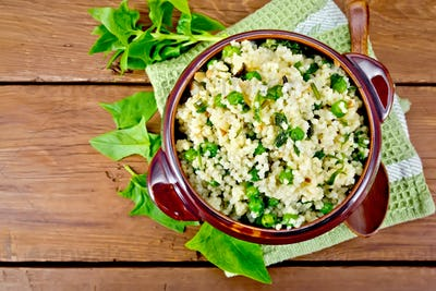 Couscous with spinach in bowl on board top