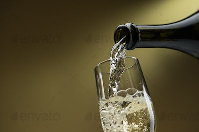 Pouring white wine into a wineglass