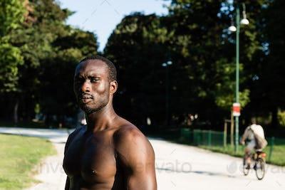 Athletic black man posing in a city park