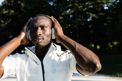 Black man listening to music in a city park